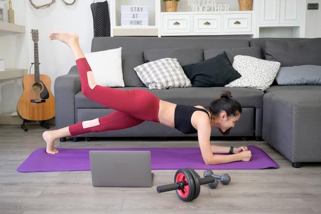Eine frau macht yoga-planken und schaut sich online-trainings-tutorials auf ihrem laptop im wohnzimmer an