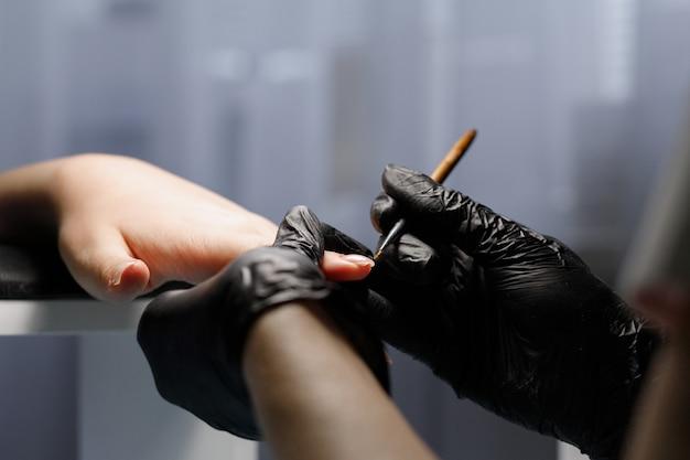 Eine frau malt einen nagel auf einem blauen nagellack in der salonnahaufnahme