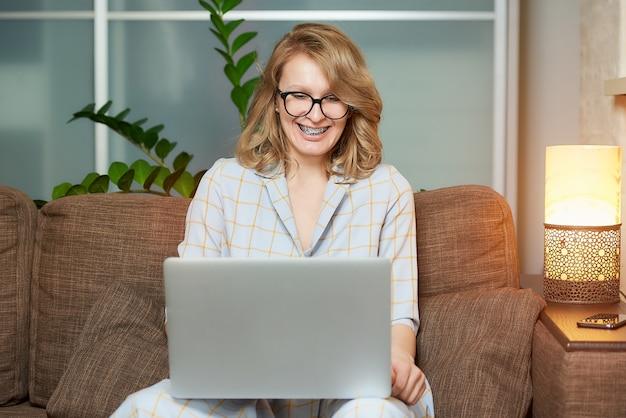 Eine frau mit brille arbeitet in ihrer wohnung an einem laptop. ein süßes mädchen, das während einer videokonferenz mit ihren kollegen zu hause lacht.