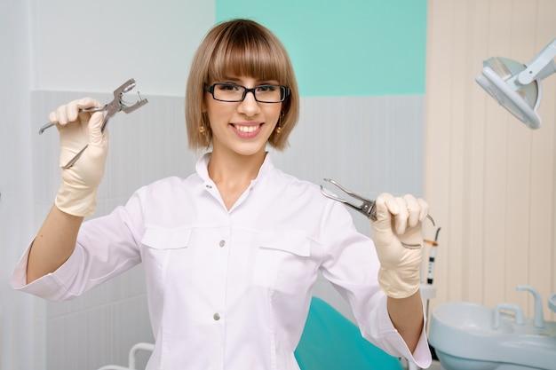 Eine frau mit brille, ein zahnarzt mit werkzeugen in den händen in einem weißen kittel, steht in der zahnarztpraxis und lächelt