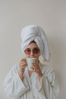 Eine frau mit brille im bademantel und handtuch im hotel trinkt kaffee aus einer weißen tasse. lifestyle freudige fotografie