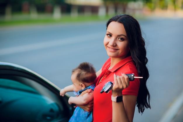 Eine frau mit einem baby im arm steht am auto und will die tür öffnen. konzept einer komplexen situation