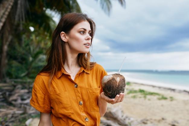 Eine frau mit einem blauen rucksack in einem gelben kleid und hut geht mit palmen am meer entlang am sand entlang