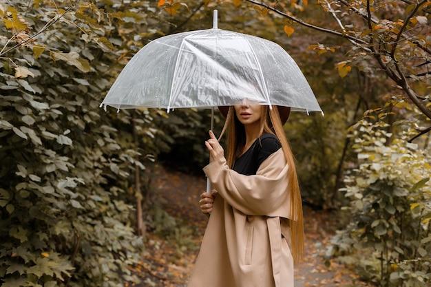 Eine frau mit einem durchsichtigen regenschirm im herbst bei einem spaziergang. nahaufnahme