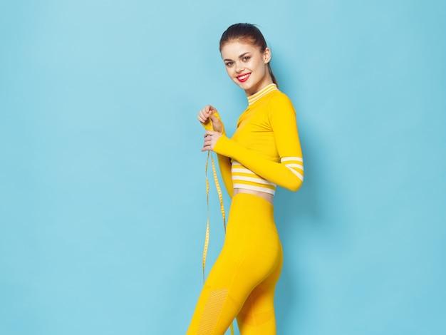 Eine frau mit einem eleganten trainingsanzug treibt sport und macht übungen, ein gelber trainingsanzug