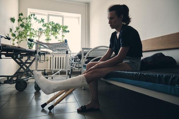 Eine frau mit einem gebrochenen bein sitzt auf einer krankenhausliege beinverletzung rehabilitation nach einer fraktur