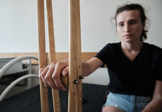 Eine frau mit einem gebrochenen bein sitzt auf einer krankenhausliege und hält medizinische krücken in der hand