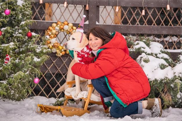 Eine frau mit einem goldenen labrador in einem schal sitzt bei einem schneefall im winter im innenhof eines wohnhauses neben einem geschmückten weihnachtsbaum und schlitten.