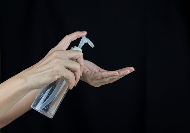 Eine frau mit einem händedesinfektionsmittel drückt gel in der hand auf schwarzem hintergrund.
