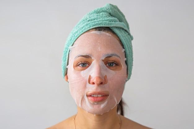 Eine frau mit einem handtuch auf dem kopf und einer maske im gesicht