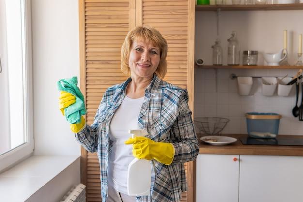 Eine frau mit einem lappen putzt und wäscht in der küche