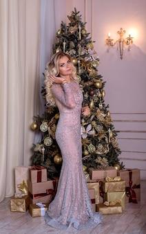 Eine frau mit einem perfekten körper in einem abendkleid hält ein glas champagner in der nähe des weihnachtsbaumes.