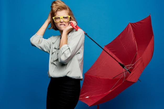 Eine frau mit einem roten regenschirm auf einem blauen in einem hellen hemd und einer gelben brille