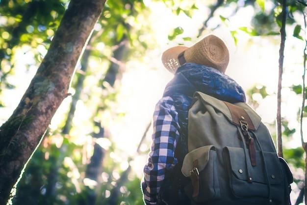 Eine frau mit einem rucksack und einem hut, die eine schöne ansicht bewundern. abenteuer in der wildnis.