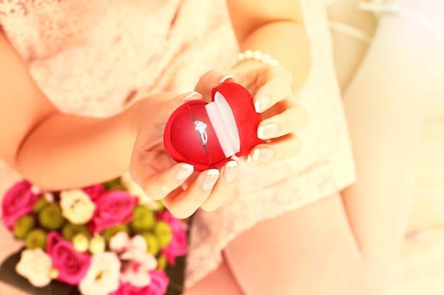 Eine frau mit einem verlobungsring in einer roten schachtel