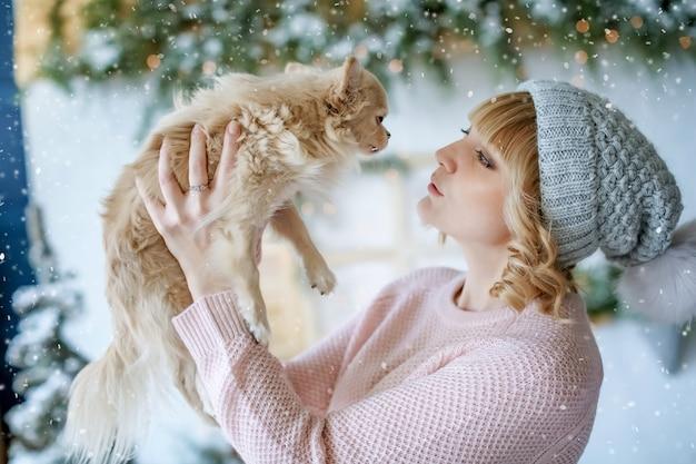 Eine frau mit einem welpen der kleinen rasse in ihren armen in einem weihnachtsfoto auf dem hintergrund der winterlandschaft.