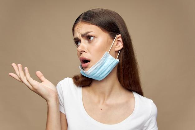 Eine frau mit einer medizinischen maske am ohr zeigt ihre hand auf einem beige- und emotionsmodell zur seite