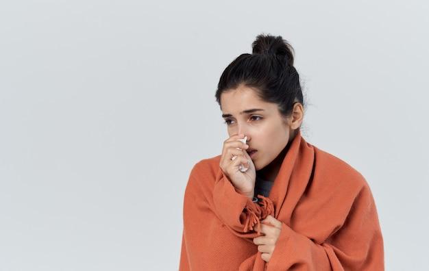 Eine frau mit einer serviette ist in ein orangefarbenes plaid auf einem hellen hintergrund gesundheitsprobleme eingewickelt