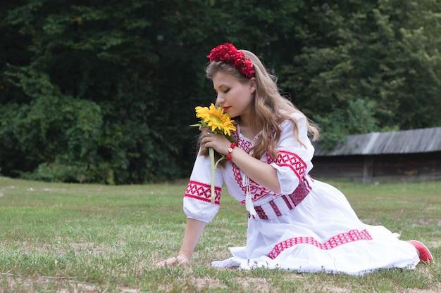 Eine frau mit einer sonnenblume, eine frau sitzt in einem kranz und einer nationaltracht im gras