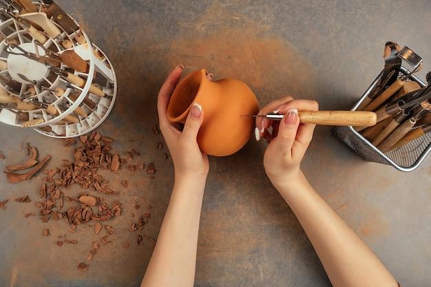 Eine frau mit einer vase aus ton in einer töpferwerkstatt. eine vase aus ton in den händen des meisters und werkzeuge auf der tischplattenansicht. potter-draufsicht. exemplar
