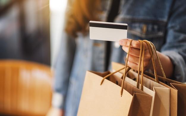 Eine frau mit einkaufstüten, die eine kreditkarte für den kauf halten und verwenden