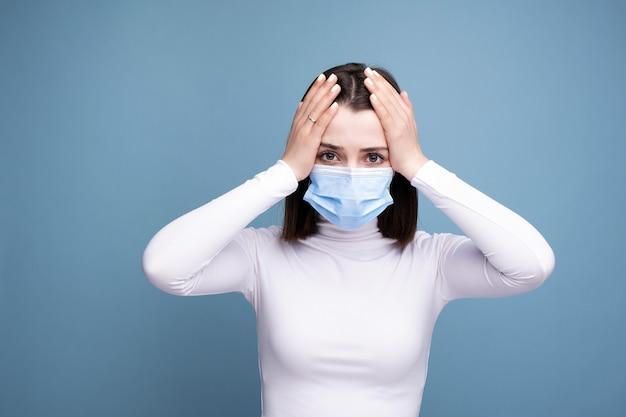 Eine frau mit erkältungssymptomen und kopfschmerzen hält im studio auf blauem hintergrund in der hand