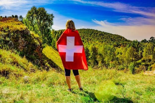 Eine frau mit europäischem aussehen hält bei sonnigem wetter die schweizer flagge vor der kulisse von bäumen und bergen. blondes mädchen mit schweizer flagge in der hand