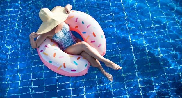 Eine frau mit hut entspannt sich auf einem aufblasbaren kreis im pool.