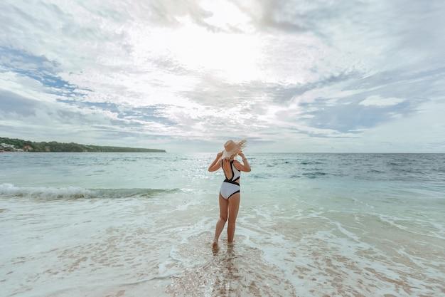 Eine frau mit hut schaut auf den sonnenuntergang am strand