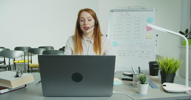 Eine frau mit kopfhörern unterrichtet eine online-klasse.