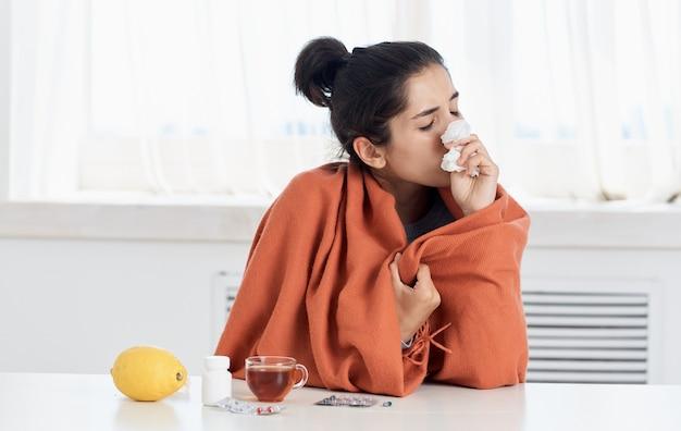 Eine frau mit laufender nase sitzt mit gelben zitronenpillen und einer tasse tee am tisch. hochwertiges foto