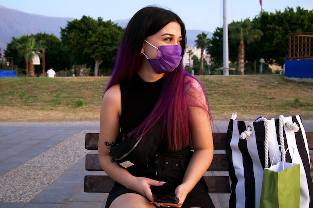 Eine frau mit lila haaren und einkaufstüten. sie trägt wegen einer virusepidemie eine lila maske auf seinem gesicht