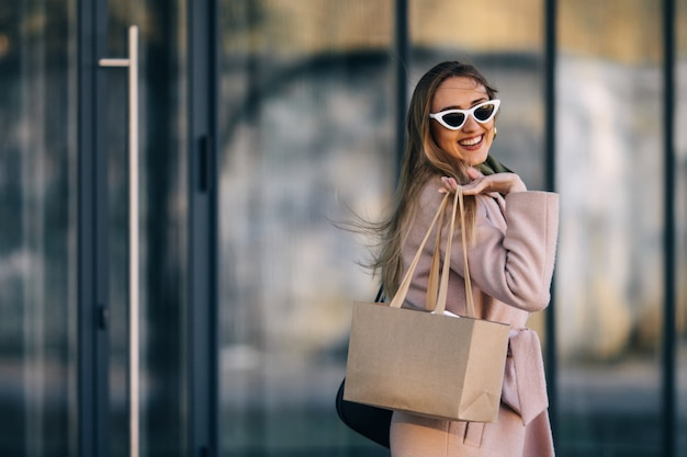Eine frau mit mantel und sonnenbrille kommt aus einer einkaufsstraße
