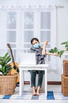 Eine frau mit maske benutzt bei der arbeit einen laptop und streckt die arme aus, um sich zu entspannen.