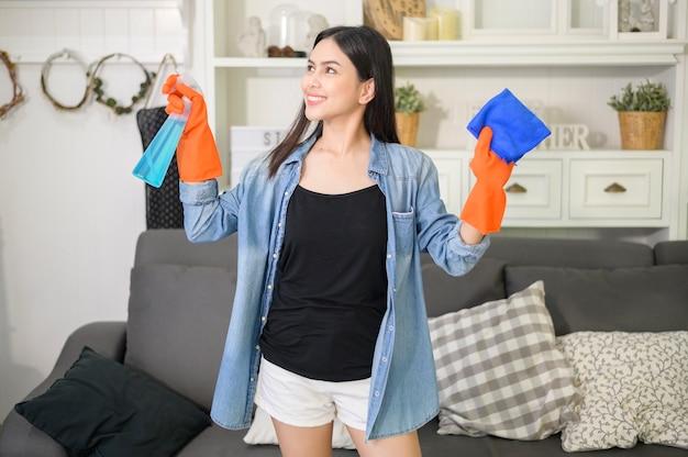 Eine frau mit reinigungshandschuhen unter verwendung von alkoholspray-desinfektionsmittel zur reinigung des hauses, gesund und medizinisch, covid-19-schutz zu hause konzept.