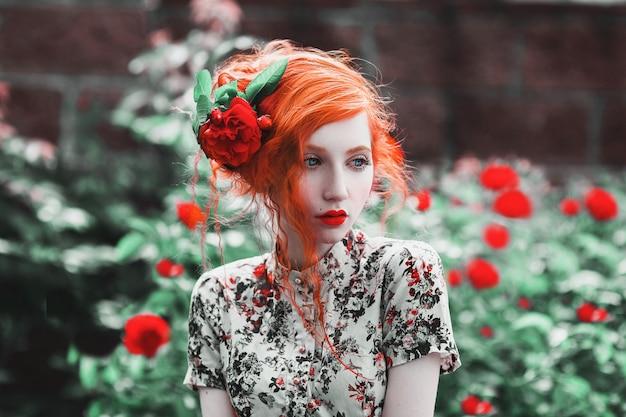 Eine frau mit rotem lockigem haar in einem blumenkleid auf dem hintergrund eines busches mit roten rosen. rothaariges mädchen mit blasser haut, blauen augen, hellem ungewöhnlichem aussehen und roten lippen und dünner taille im garten.