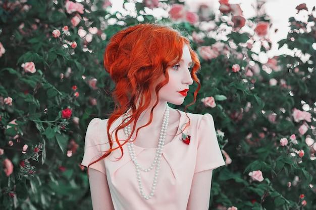 Eine frau mit rotem lockigem haar in einem kleid auf einem hintergrund des pfirsichrosenbusches. rothaariges mädchen mit blasser haut, blauen augen, einem hellen, ungewöhnlichen aussehen und roten lippen und einer dünnen taille mit perlen am hals