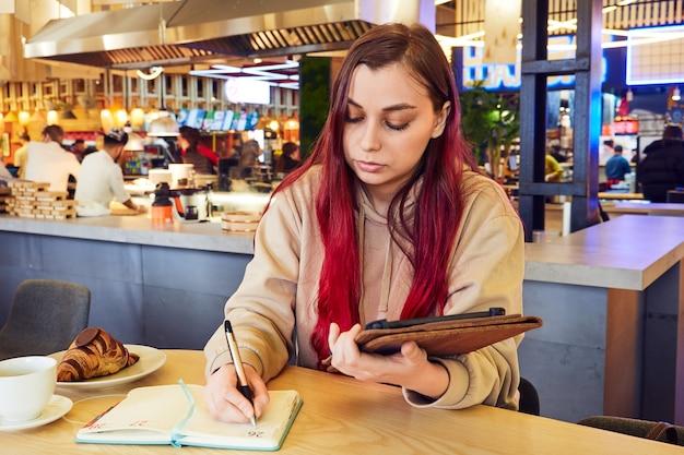 Eine frau mit roten haaren arbeitet fern in einem café und schreibt in ein tagebuch