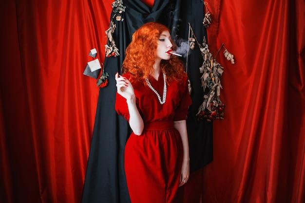 Eine frau mit roten haaren in einem rot sitzenden kleid mit einer zigarette im mund. rothaariges mädchen mit blasser haut und blauen augen mit einem hellen ungewöhnlichen aussehen mit perlen um den hals. noir bild
