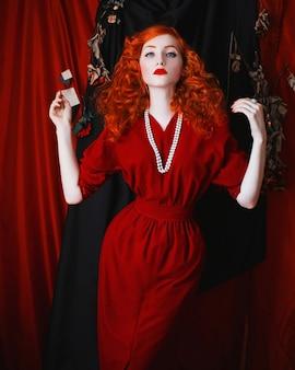 Eine frau mit roten haaren in einem roten passenden kleid. rothaariges mädchen mit blasser haut und blauen augen mit einem hellen, ungewöhnlichen aussehen und perlen um den hals. noir frau
