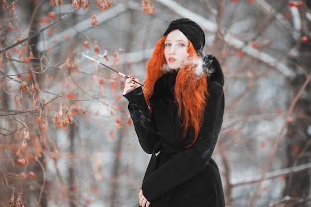 Eine frau mit roten haaren in einem schwarzen mantel an eines winterwaldes mit einem mundstück in der hand. rothaariges mädchen mit hellem auftritt mit einem turban auf dem kopf mit einer zigarette