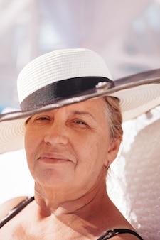 Eine frau mit strohhut nahaufnahmeporträt einer älteren glücklichen frau in einem weißen strohhut, die in einem ...