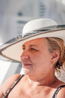Eine frau mit strohhut profilporträt einer charmanten frau in einem weißen strohhut, die sich am strand entspannt...
