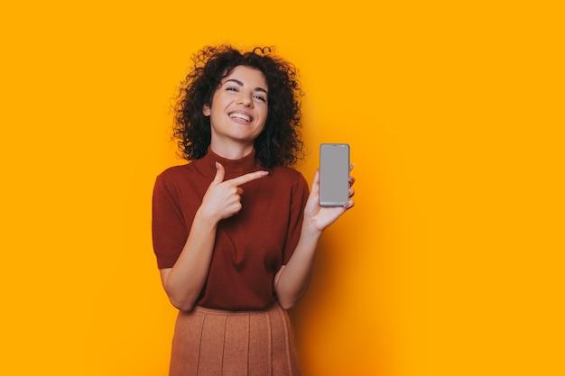 Eine frau mittleren alters, die auf ihr neues telefon zeigt und versucht, die neuen funktionen herauszufinden, fühlt sich in ihrem roten pullover sicher.