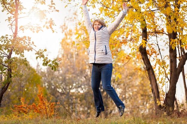 Eine frau mittleren alters geht im herbstpark zwischen den bäumen spazieren