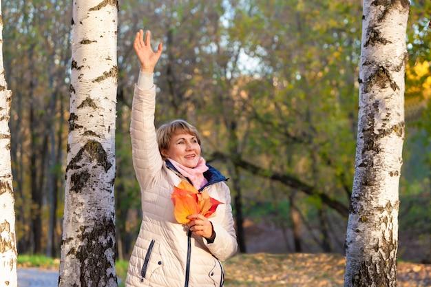 Eine frau mittleren alters geht in einem herbstpark spazieren