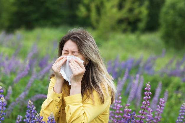 Eine frau niest in ein taschentuch gegen ein konzept der blühenden lupinen der blumenallergie