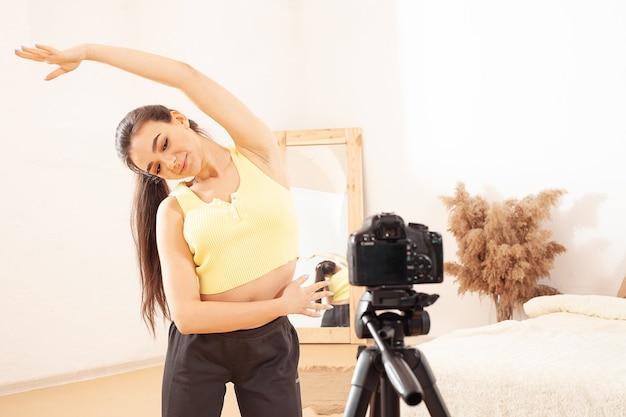 Eine frau nimmt ein video für ihren kanal im internet auf. blogger. zeigt, wie man richtig trainiert