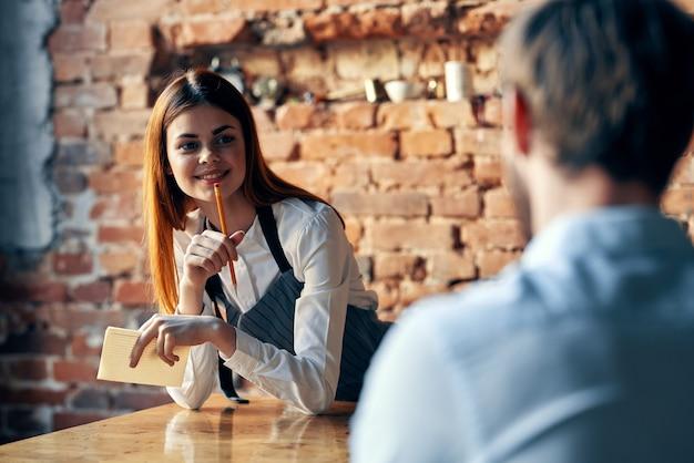 Eine frau nimmt eine bestellung von einem mann in einem café entgegen, das einen kellner bedient