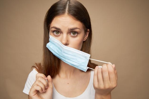 Eine frau nimmt eine medizinische maske von ihrem gesicht auf einem isolierten hintergrund ab
